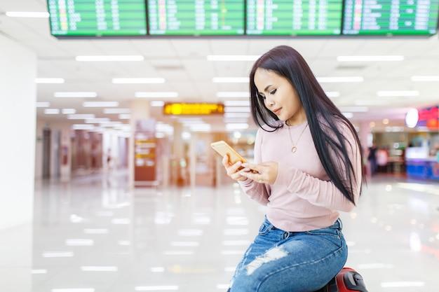A mulher asiática que senta-se no uso de bagagem do telefone celular verifica dentro a linha aérea em linha do bilhete no aeroporto internacional. Foto Premium