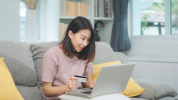 A mulher asiática que usa o comércio eletrônico da compra do portátil e do cartão de crédito, fêmea relaxa sentindo a compra online feliz que senta-se no sofá na sala de visitas em casa. as mulheres do estilo de vida relaxam em casa o conceito. Foto gratuita
