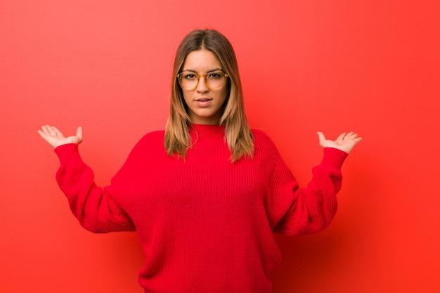 A mulher autêntica nova carismática autêntica nova dos povos contra uma parede faz a escala com braços, sente feliz e segura. Foto Premium