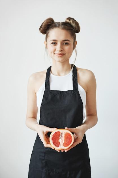 A mulher bonita alegre com os bolos no avental que sorri guardando a metade da toranja cede dentro a parede branca. Foto gratuita