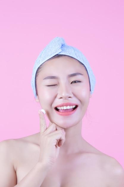 A mulher bonita ásia está lavando sua face no fundo cor-de-rosa. Foto gratuita