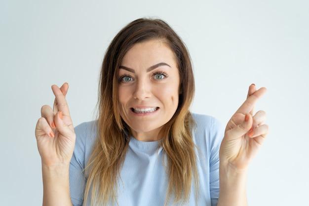 A mulher bonita de sorriso que mostra cruzou o gesto dos dedos. senhora fazendo desejo. Foto gratuita