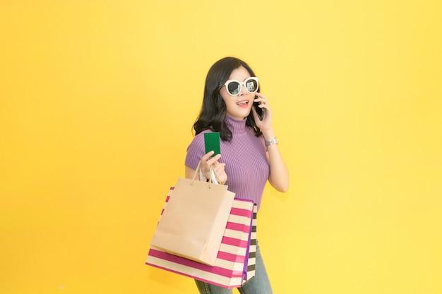A mulher bonita está comprando na alameda usando o cartão de crédito vidros vestindo da mulher e forma guardar do saco de compras no armazém. Foto Premium