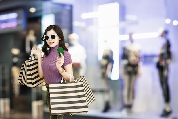 A mulher bonita está comprando na alameda vidros vestindo e chapéu da mulher que guardam a forma do saco de compras no armazém. Foto Premium