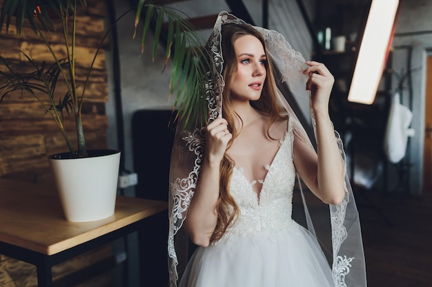 A mulher bonita posando em um vestido de noiva. Foto Premium
