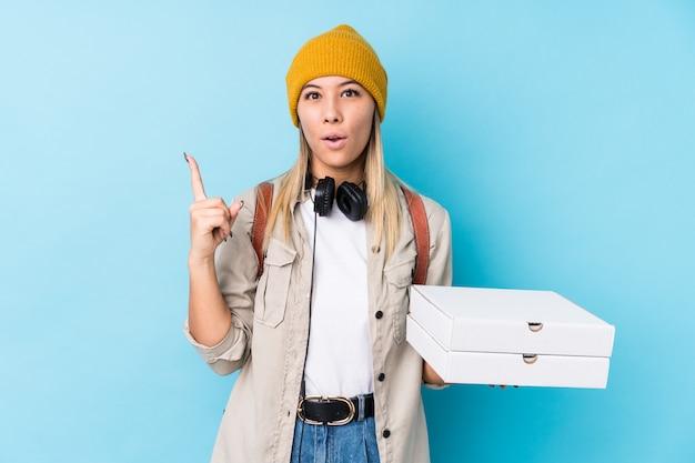 A mulher caucasiano nova que mantem pizzas isolou-se tendo alguma grande ideia, conceito da faculdade criadora. Foto Premium