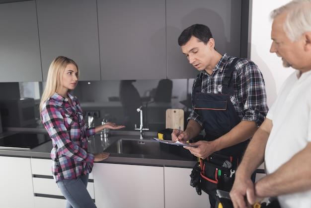 A mulher chamou dois encanadores para consertar a pia da cozinha. Foto Premium
