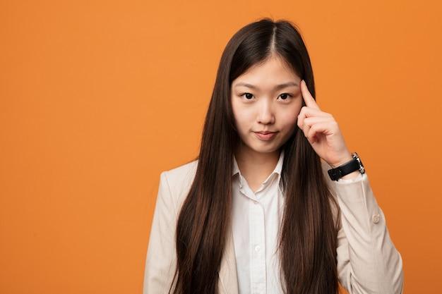 A mulher chinesa do negócio novo que aponta o templo com o dedo, pensando, focalizou em uma tarefa. Foto Premium