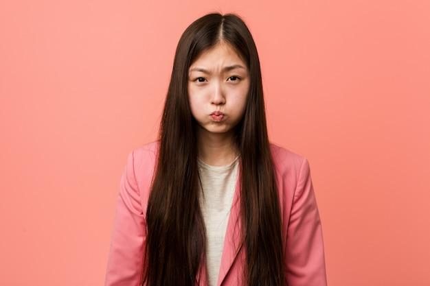 A mulher chinesa do negócio novo que veste o terno cor-de-rosa funde bochechas, tem expressão cansado. Foto Premium
