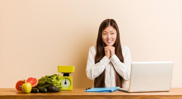 A mulher chinesa do nutricionista novo que trabalha com seu portátil mantém as mãos sob o queixo, está olhando felizmente de lado. Foto Premium