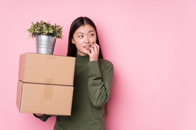 A mulher chinesa nova que guarda caixas relaxou o pensamento sobre algo que olha um espaço em branco. Foto Premium