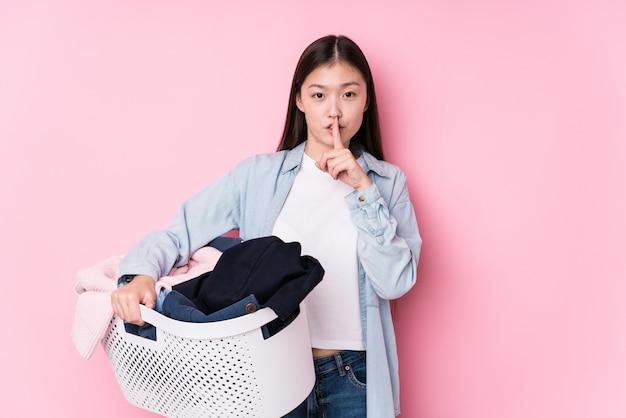 A mulher chinesa nova que pega a roupa suja isolou mantendo um segredo ou pedindo o silêncio. Foto Premium