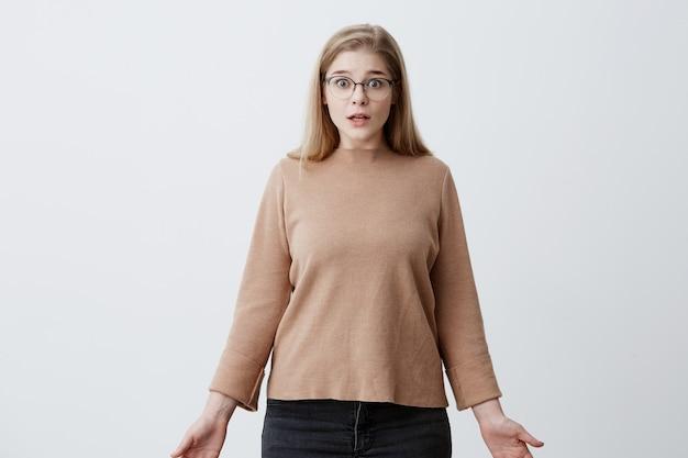 A mulher chocada estupefata olha com expressão chocada, com os olhos esbugalhados, atônita ao ouvir notícias chocantes. mulher branca em óculos tem olhar intrigado, isolado Foto gratuita