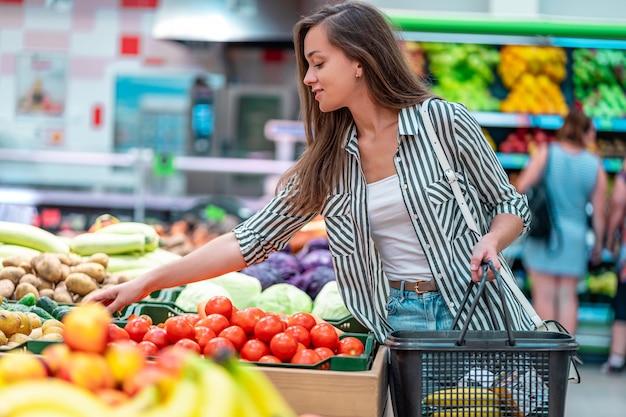 A mulher com cesto de compras escolhe tomates vermelhos frescos no departamento vegetal do supermercado. cliente que compra comida na mercearia Foto Premium