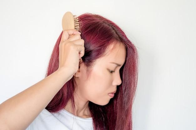 A mulher comping seu cabelo lentamente e ela tem problema de perda de cabelo Foto Premium