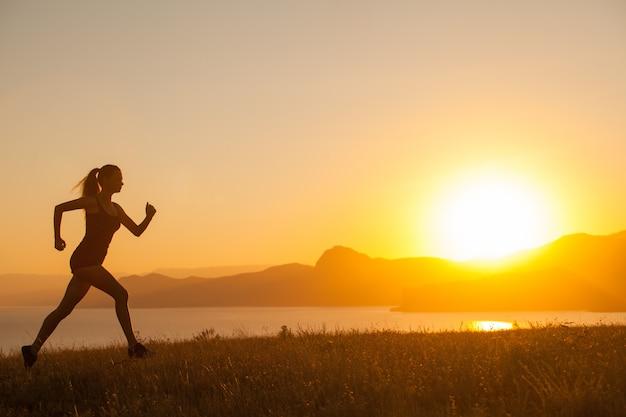A mulher corre nas montanhas no oceano. Foto Premium