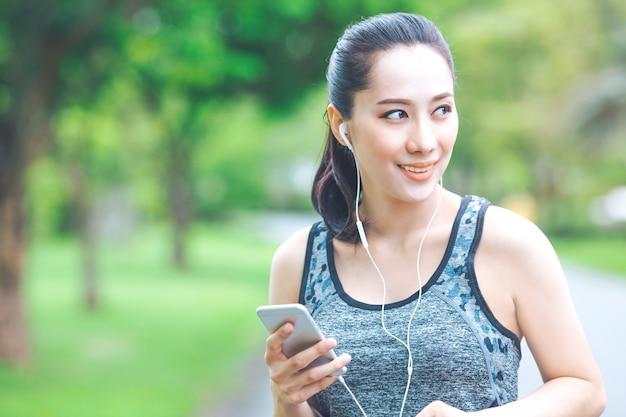 A mulher da aptidão está escutando a música de seu telefone celular ao correr no parque. Foto Premium