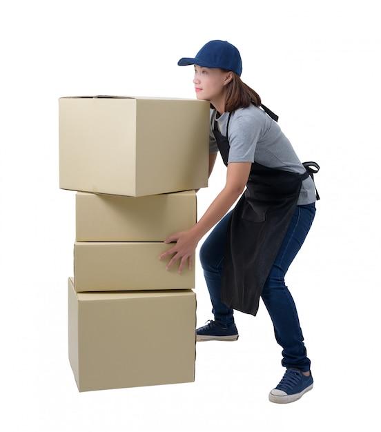 A mulher da entrega na camisa e no avental cinzentos está mantendo caixas isolou a camisa e o avental. ela levantando caixas de peso pesado isoladas Foto Premium