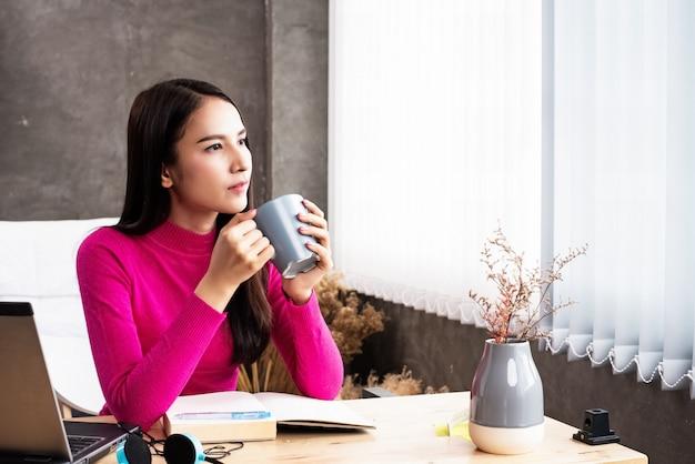 A mulher de beleza segurando a xícara de café de cerâmica na mão, olhando para fora da janela, relaxar o tempo entre o trabalho, luz embaçada em torno de Foto Premium