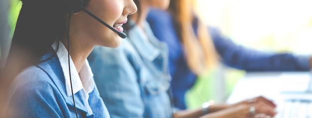 A mulher de negócio atrativa asiática nos ternos e nos auriculares está sorrindo ao trabalhar com o computador no escritório. assistente de serviço ao cliente, trabalhando no escritório Foto Premium