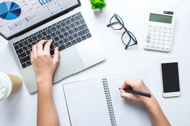 A mulher de negócio está tomando notas e está usando calculadoras e portáteis em uma tabela branca. vista do topo. Foto Premium