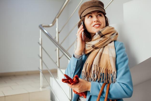 A mulher de negócio no revestimento está nas escadas na alameda com smartphone. compras. moda Foto Premium