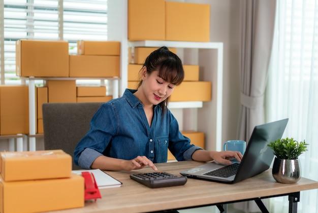 A mulher de negócios asiática bonita do proprietário do adolescente encantador que trabalha em casa para compras on-line, calcula o preço das mercadorias com o laptop com equipamento de escritório, conceito de estilo de vida do empresário Foto Premium