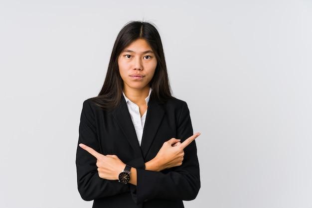A mulher de negócios asiáticos jovens aponta lateralmente, está tentando escolher entre duas opções. Foto Premium