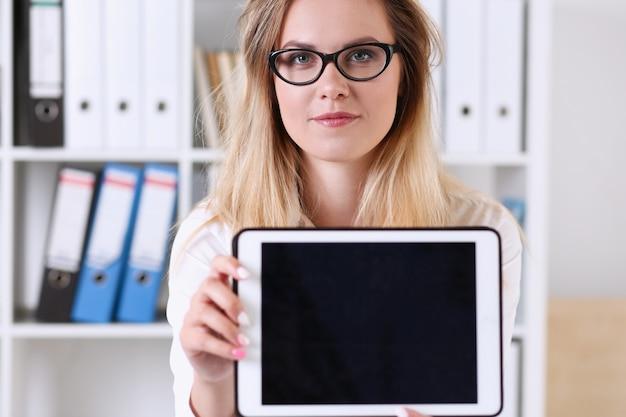 A mulher de negócios bonita que veste o retrato dos vidros no escritório que mantem uma tabuleta à disposição que senta-se na tabela que sorri e que olha o professor da câmera expressa o sucesso que verifica os papéis de teste. Foto Premium