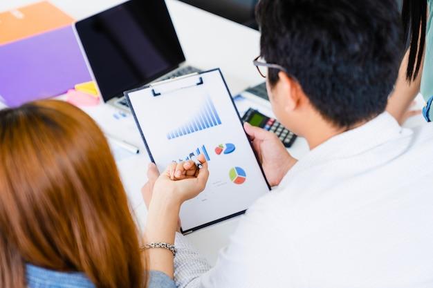 A mulher de negócios nova explica o detalhe do plano de marketing na folha de dados para team com o portátil na tabela. Foto Premium