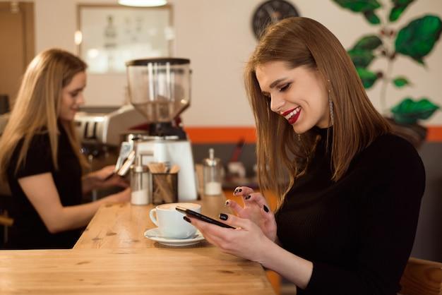 A mulher de sorriso de um bom humor aprecia a xícara de café que senta-se em um café. Foto Premium