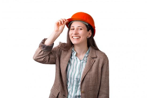 A mulher de sorriso larga gosta de vestir um capacete de segurança no fundo branco. Foto Premium