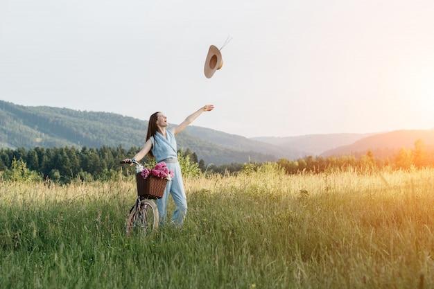 A mulher de sorriso que joga um chapéu e aprecia a natureza da montanha durante o por do sol. Foto Premium