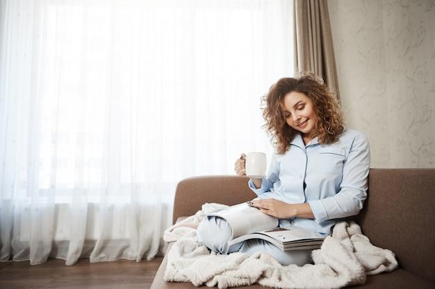 A mulher decidiu tratar-se em um bom dia. retrato de mulher atraente cabelos cacheados feminino sentado no sofá de pijama, tomando café, desfrutando de ler revista, cobrindo os pés com cobertor Foto gratuita