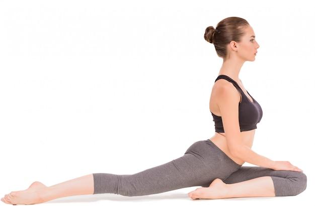 A mulher desportiva nova que faz o esticão exercita no estúdio. Foto Premium