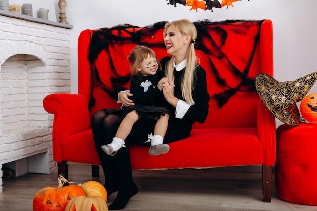 A mulher e a menina têm um tempo engraçado no sofá vermelho. emoção e halloween Foto Premium