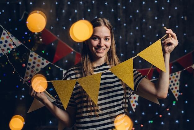 A mulher em casa que pendura bandeiras do partido das luzes de natal decora artigos para a celebração do ano novo Foto Premium
