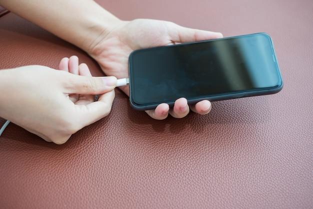 A mulher entrega a carga da bateria no telefone móvel esperto no sofá em casa. tecnologia, compartilhamento múltiplo e conceitos de estilo de vida Foto Premium