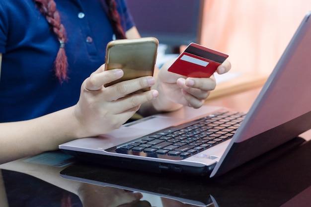 A mulher entrega guardar o cartão de crédito usando-se no telefone e no portátil espertos. Foto Premium