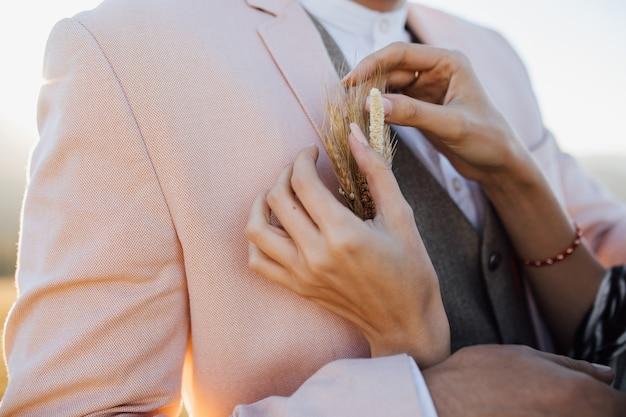 A mulher está consertando uma botoeira nupcial elegante a um homem Foto gratuita