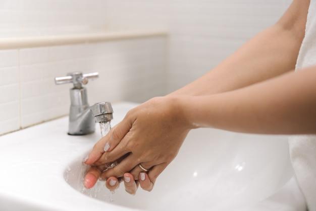 A mulher está lavando sua mão sob a água corrente no banheiro. Foto Premium