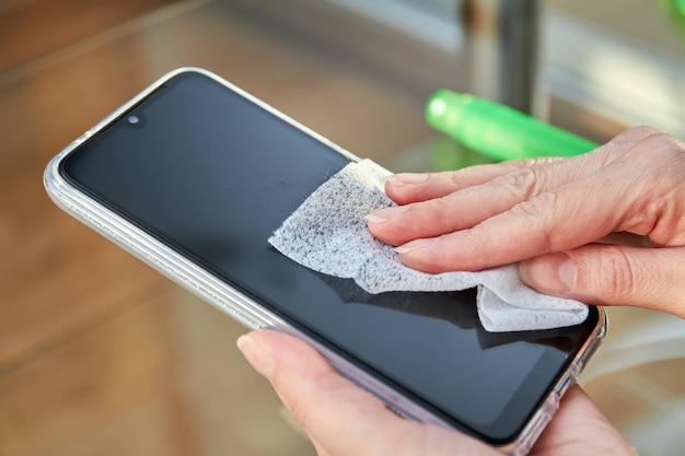 A mulher está limpando um smartphone com um jato de desinfetante para as mãos com álcool aerossol e pano descartável em casa. precauções contra vírus Foto Premium