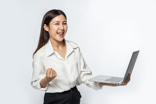A mulher estava vestindo uma camisa branca e calça escura, segurando um laptop e fingindo estar feliz Foto gratuita