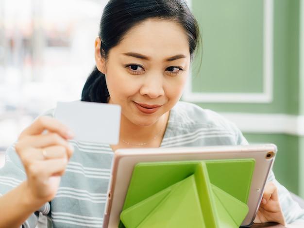 A mulher feliz está usando um cartão de crédito branco do modelo para a compra em linha na tabuleta. Foto Premium