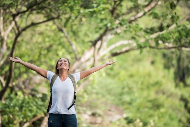 A mulher feliz nova com a trouxa que levanta a mão aprecia com natureza. Foto gratuita