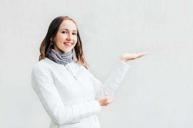 A mulher feliz que guarda sua mão para apresentar qualquer coisa e olha na lente. Foto Premium