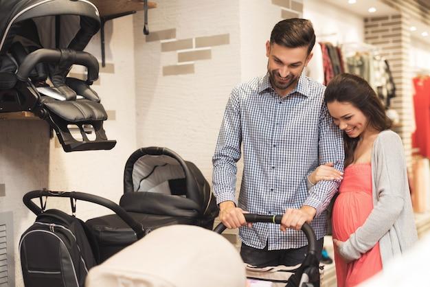 A mulher junto com um homem escolhe um carrinho de bebê. Foto Premium