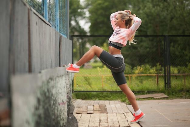 A mulher loura da aptidão saudável bonita no desgaste do esporte da forma que faz o esporte exercita no campo atlético. Foto Premium