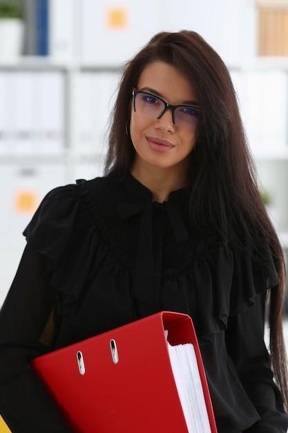 A mulher moreno de sorriso bonita segura na pasta vermelha dos braços Foto Premium