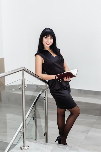A mulher moreno feliz bonita nova vestiu-se em um terno de negócio preto que trabalha com um caderno, estando em um escritório, sorrindo. Foto Premium